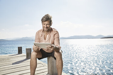 Smiling man sitting on jetty looking at tablet - PDF01208