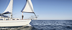 Mature man standing on his sailing boat looking at distance - PDF01217