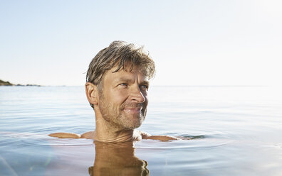 Portrait of smiling man bathing in the sea - PDF01226