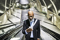 Businessman with smartphone reading messages on escalator - FMKF03785