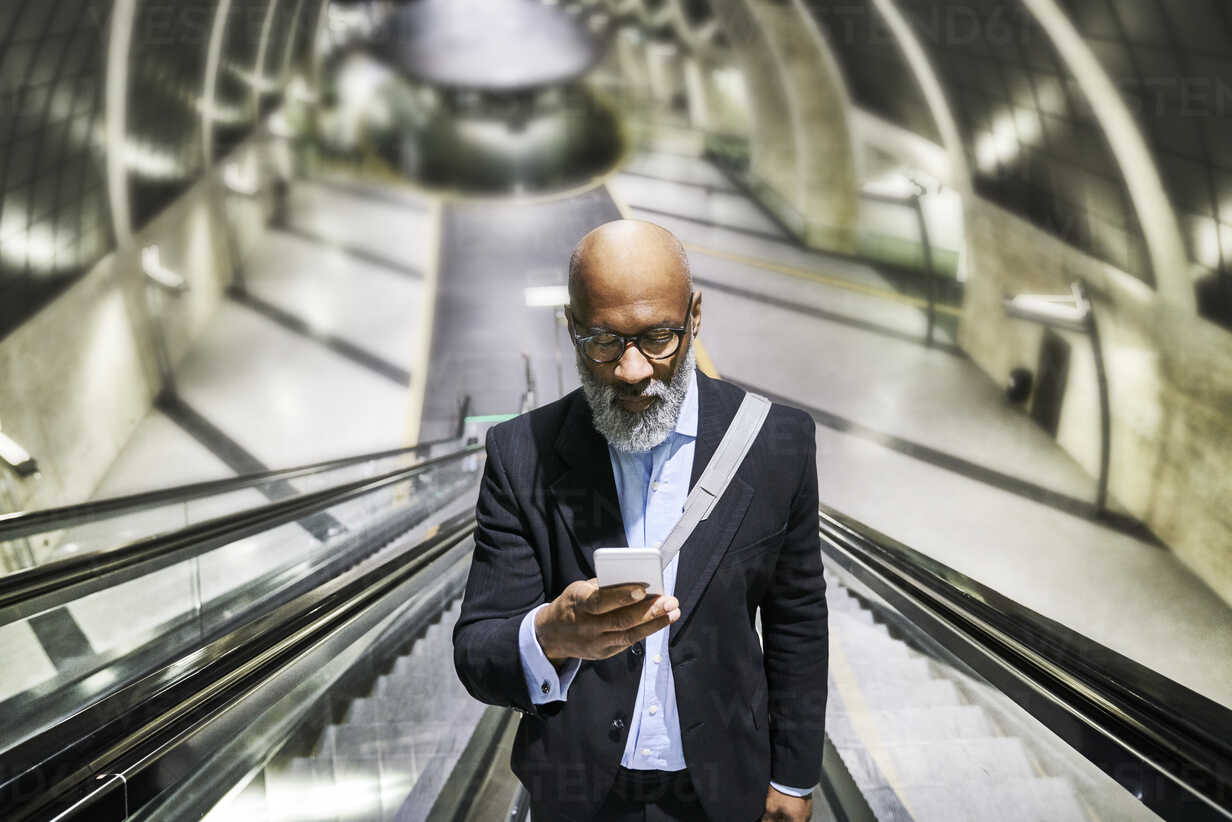 Businessman with smartphone reading messages on escalator - FMKF03785 - Jo Kirchherr/Westend61