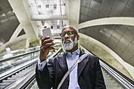 Businessman with smartphone reading messages on escalator - FMKF03788