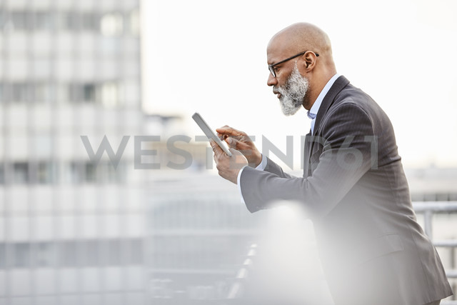 Businessman using digital tablet on rooftop - FMKF03797 - Jo Kirchherr/Westend61