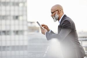 Businessman using digital tablet on rooftop - FMKF03797