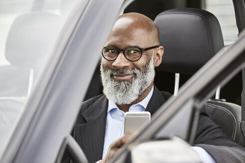Businessman sitting in car using smartphone - FMKF03803