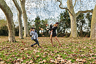 Mother playing with her daughter in autumnal park - MGOF03178