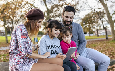 Family sitting on bench in autumnal park looking at tablet - MGOF03184