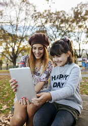 Mother and little daughter taking selfie with tablet in autumnal park - MGOF03187