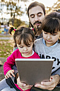 Father with his little daughters looking at tablet - MGOF03196