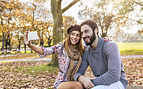Happy couple taking selfie with smartphone in autumnal park - MGOF03199