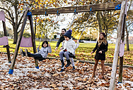 Happy family having fun with swings in autumn - MGOF03208