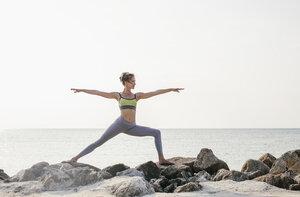 Woman practicing yoga on the beach - MOMF00058