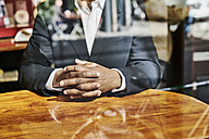 Mature businessman sitting in snack bar - FMKF03816