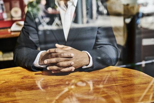 Mature businessman sitting in snack bar - FMKF03816