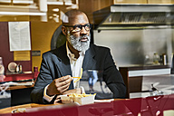 Mature businessman sitting in snack bar, eating French fries - FMKF03819