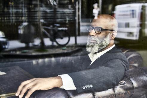 Mature businessman sitting in armchair, thinking - FMKF03822