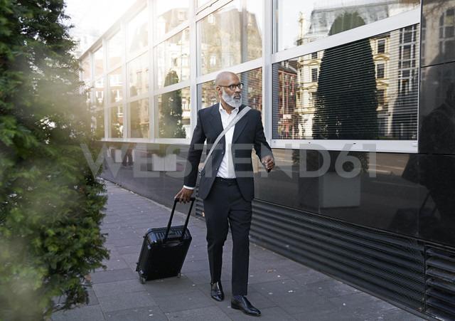 Mature businessman walking in street, pulling trolley bag - FMKF03825 - Jo Kirchherr/Westend61