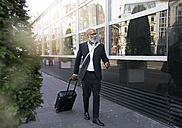Mature businessman walking in street, pulling trolley bag - FMKF03825