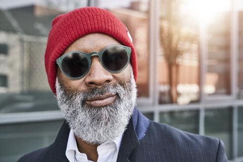 Mature businessman wearing red cap - FMKF03831