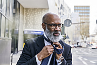 Mature businessman tying tie in the street - FMKF03834