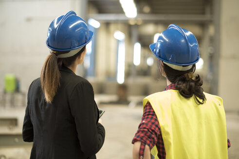 Women working together in concrete factory - JASF01583