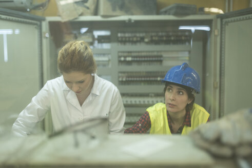 Female colleagues working at control panel in a factory - JASF01598
