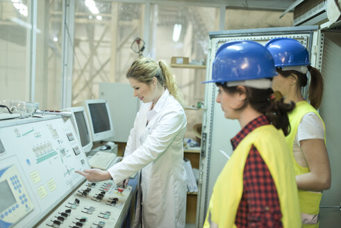 Female colleagues working at control panel in a factory - JASF01601