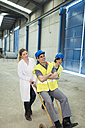 Female workers pushing colleague on a hand truck - JASF01604