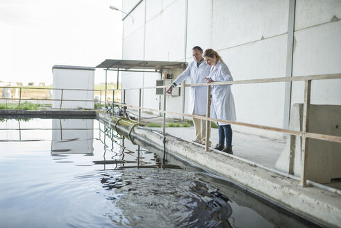 Scientists observing water surface in a factory - JASF01622