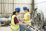 Female skilled workers in concrete factory adjusting machine - JASF01652
