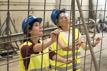 Female skilled workers in concrete factory setting up iron reinforcement - JASF01655