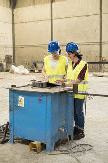 Female skilled workers in concrete factory adjusting machine - JASF01658