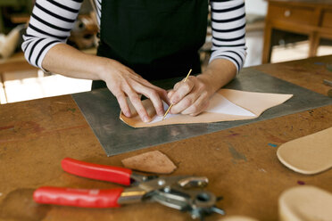 Close-up of shoemaker working on template in her workshop - VABF01299