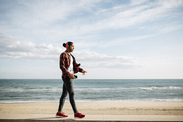 Young man walking on wall in front of the beach promenade listening music with headphones - JRFF01291