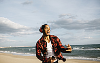 Portrait of young man on the beach singg and dancing while listening music with headphones - JRFF01294