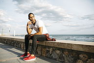 Young man sitting on wall at beach promenade looking at distance - JRFF01300