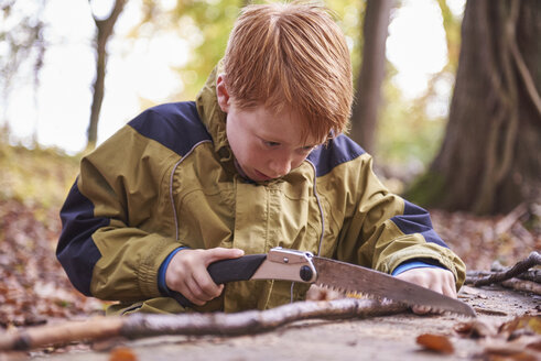 Redheaded boy treating branch with bow in autumnal forest - JEDF00286