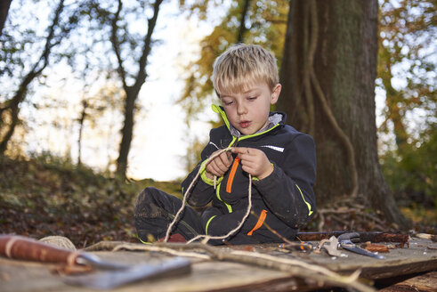 Portrait of blond little boycutting rope with knife outdoors - JEDF00292