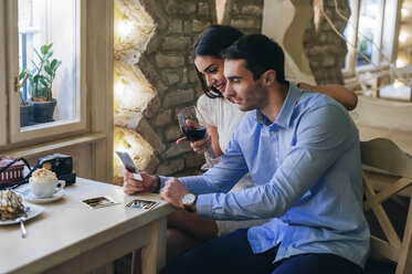 Young couple watching instant photos in a restaurant - MOMF00088