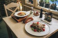 Two dishes ready to eat on a restaurant table - MOMF00094