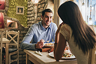 Portrait of happy young man having dinner with his girlfriend in a restaurant - MOMF00106