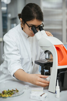 Laboratory technician using microscope in lab - ZEDF00565