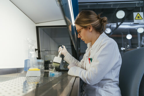 Laboratory technician pipetting in lab - ZEDF00568