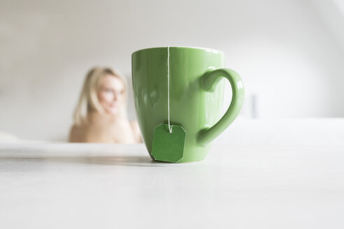 Green mug with tea bag and blond woman in the background - CHPF00386