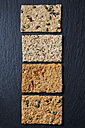 Row of four various slices of grain crispbreads on slate - CSF28261