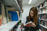 Female student reading book in a library - ZEDF00591
