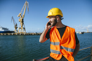 Smiling port worker talking on cell phone - KIJF01381