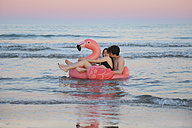 Couple in love floating with inflatable pink flamingo on the sea at sunset - RTBF00820