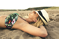 Young woman wearing a hat lying on the beach with closed eyes - DAPF00680
