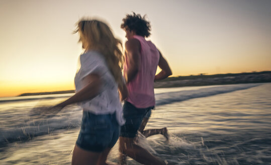 Friends holding hands and running into the sea at dusk - DAPF00683